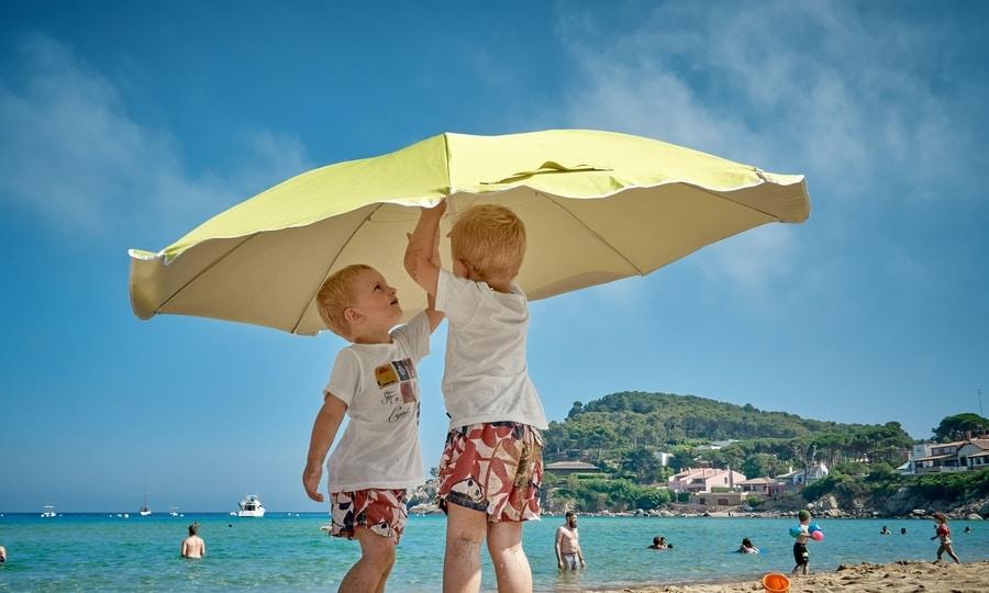 Schoolvakanties regio's in Nederland. Op de foto ter illustratie twee kinderen die een parasol opzetten op het strand. Typisch vakantie tafereel